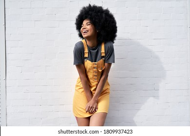 Happy stylish African American young woman wears yellow trendy sundress with Afro hair laughing looking away standing against white brick wall outdoor background. Smiling black hipster woman portrait