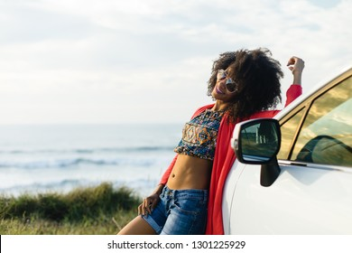 Happy stylish black woman relaxing on a car trip to the coast. Fashionable afro hair model on vacation towards the sea.