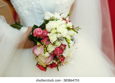 Happy stylish bride in white dress with bouquet of roses