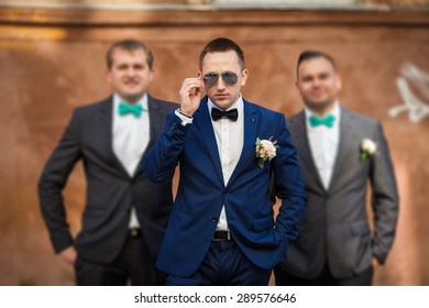 happy stylish elegant groom with bestman the background of old city