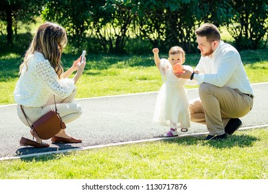 happy and stylish family in the summer in the park. family photosession of beautiful mother, bearded father and cute daughter looking at phone