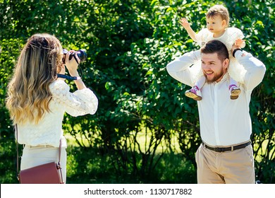 happy and stylish family in the summer park. family photosession woman photographer photographing bearded husband and cute daughter looking at camera