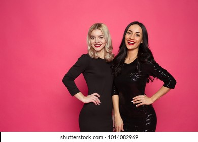 Happy stylish fashion girl friends. Two beautiful smiling modern women in little black dresses posing in front of the camera on a pink background.