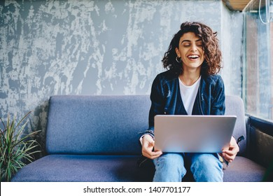 Happy stylish female blogger laughing while chatting with friends in social networks on laptop device using wireless internet in coworking.Positive young woman doing shopping online on website
