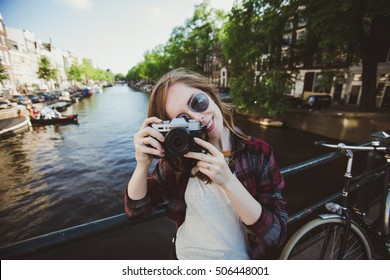 Happy stylish girl photographer with a compact film camera in Amsterdam, Netherlands. Pretty female student travels abroad and takes pictures for her blog.