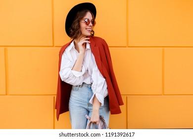 Happy stylish girl posing on yellow background. Street fashion look. Orange jacket, black hat.