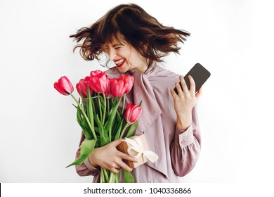 happy stylish girl smiling and dancing with phone and holding pink tulips and gift box on white background. happy mothers or womens day concept. emotional moment of happiness