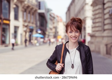 Happy Stylish Girl in Trendy Outfit with Shoulder Bag, Walking at the City Street and Showing Toothy Smile at the Camera.