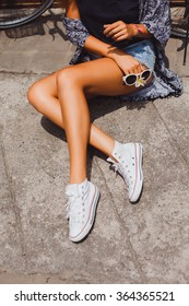 Happy stylish hipster girl,white Sneakers,Colorful summer portrait of an attractive young woman with sunglasses,Outdoor fashion closeup portrait of young pretty woman in summer sunny day on grass
