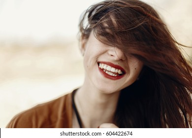 happy stylish hipster traveler woman having fun waving hair and smiling, gypsy boho girl. wanderlust summer travel. atmospheric moment. space for text.