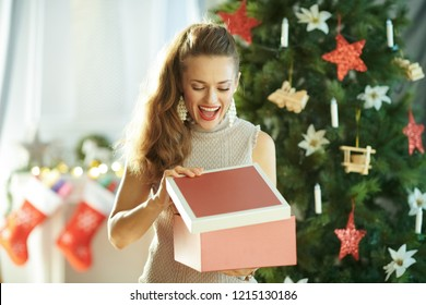 happy stylish housewife near Christmas tree opening Christmas present box