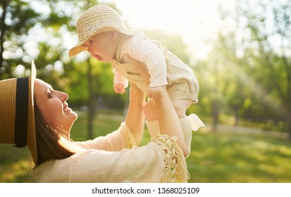 Happy stylish and loving family. mother playing with her baby outdoor. lovely baby smiles and enjoys. Mother's day concept. Lovely family spends summer day outside