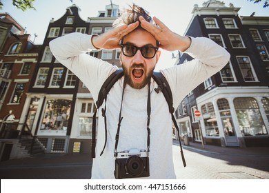 Happy stylish man takes selfie photo in Amsterdam, Netherlands. Student travels abroad and takes pictures for his blog.