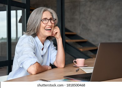 Happy stylish mature middle aged business woman wearing glasses laughing sitting at workplace desk with laptop. Cheerful positive older grey-haired businesswoman having fun working alone in office.