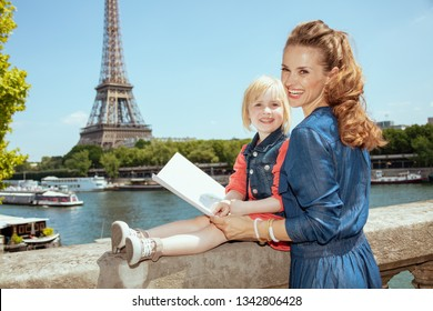 happy stylish mother and child tourists with map near the parapet on the embankment of the river Seine not far from Eiffel tower in Paris, France.