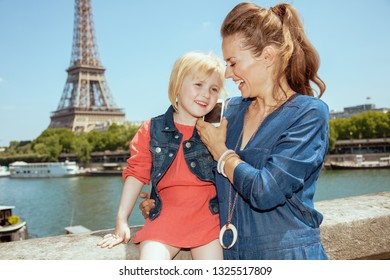 happy stylish mother and daughter travellers near the parapet on the embankment of the river Seine not far from Eiffel tower in Paris, France speaking on a cell phone.