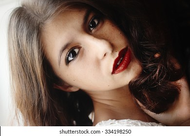 happy stylish outstanding vintage brunette girl with curly short hair and red lips in the morning