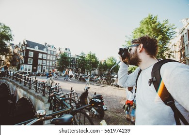 Happy stylish photographer taking a photo of Amsterdam canals, Netherlands. Student travels abroad and takes pictures for his blog.