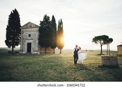Happy stylish smiling couple walking in Tuscany, Italy on their wedding day.