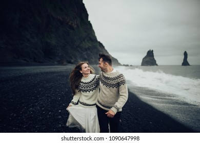 Happy stylish smiling couple walking and kissing in Iceland , on their wedding day.