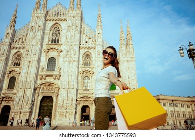 happy stylish solo traveller woman in white t-shirt and sunglasses rejoicing walking with shopping bags in the front of Duomo in Milan, Italy.