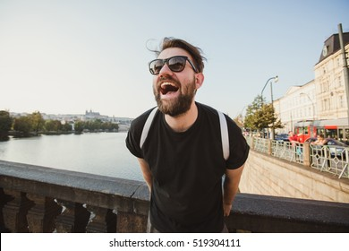 Happy stylish tourist on Charles Bridge, Prague, Czech Republic. Handsome bearded man travelling in Europe.