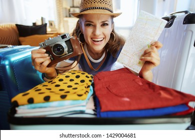 happy stylish tourist woman in blue t-shirt with retro film photo camera and map packing for summer travel in the modern house in sunny summer day.