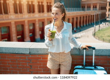 happy stylish tourist woman with trolley bag drinking green smoothie and looking into the distance in the front of Puerta de Atocha