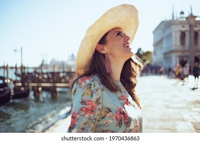 happy stylish traveller woman in floral dress with hat exploring attractions on embankment in Venice, Italy.