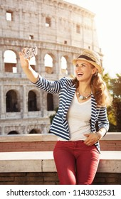 happy stylish traveller woman in a straw hat in the front of Colosseum taking selfie with phone