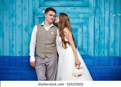 Happy stylish wedding couple having fun against blue background