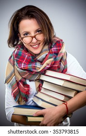 Happy stylish woman in a colorful winter scarf and eyeglasses holding a pile of hardcover books under her arm as she smiles at the camera
