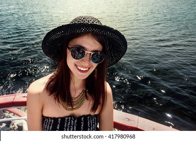 happy stylish woman hipster in fashionable sunglasses smiling and sailing on boat, summer travel concept, space for text