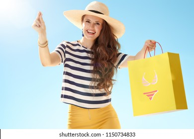 happy stylish woman in straw hat against blue sky with yellow shopping bag with bikini fingers snapping