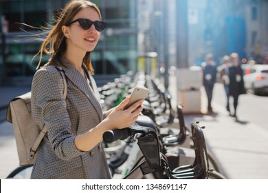 Happy stylish woman taking bike via bike renting services in the city center, Happy smiling student using bike sharing app on smart phone outdoor