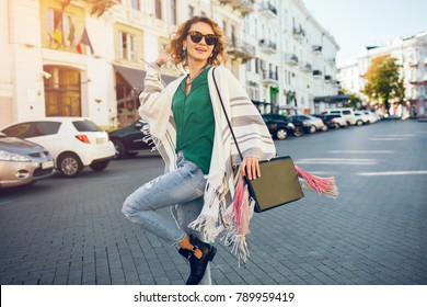 happy stylish woman walking with handbag in jeans and cape, spring apparel, fashion trendy clothes, bright sunny day, smiling, sunglasses, accessories with fringe