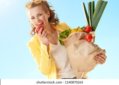 happy stylish woman in yellow jacket with paper bag with groceries biting an apple against blue sky