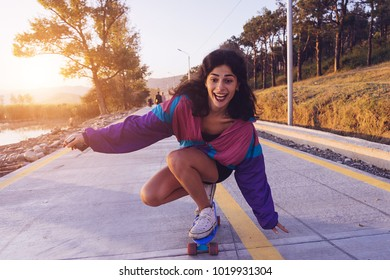 happy stylish young girl skateboarding on the street