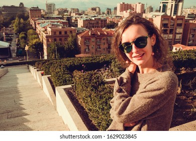 Happy stylish young woman in green sunglasses enjoy warm fall in Yerevan. Viewpoint cascade complex. City tour. Girl travel to Armenia. Tourism concept. Sunny autumn day. Armenian architecture.