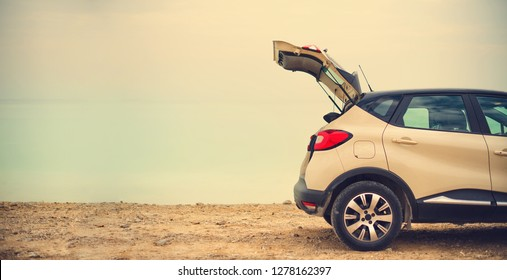 Happy stylish young woman traveler on beach road sitting on white crossover car, holding hat in hand. Banner. Travel, summer vacation, holiday, freedom concept. Digital detox.