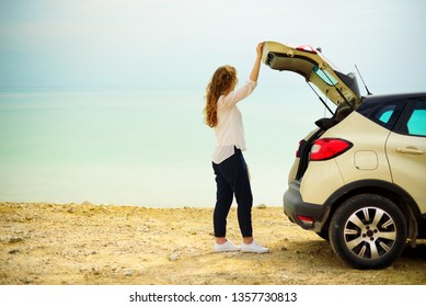 Happy stylish young woman traveler on beach road near white crossover car, holding hat in hand. Banner. Travel, summer vacation, holiday, freedom concept. Digital detox.