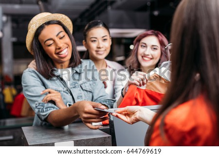 0ca68507d851d Happy stylish young women paying with credit card in shopping mall, young  girls shopping concept