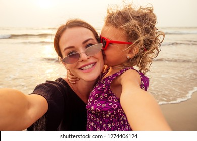 Happy stylishly mother and daughter taking selfie at sandy beach on a sunset.mothers Day.little girl blonde and beautiful woman taking pictures on the phone tourism abroad online video calling
