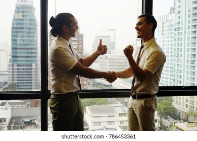 the happy and success business man with window view of the high building office.Two men shaking hands standing at big window with urban cityscape, confident business partner. forming good relationship