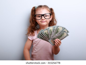 Happy success kid girl in eye glasses holding in hand american dollars and joying. Portrait on blue background with empty copy space