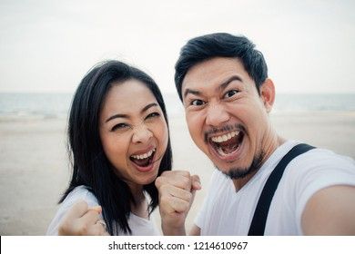 Happy and success Yeah face of asian couple tourist on romantic beach vacation trip.