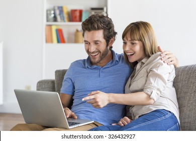 Happy success young couple with laptop on sofa in modern white apartment.