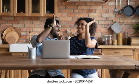 Happy successful Afro American couple celebrating financial achieve at laptop, giving high five. Married man and woman getting income, profit, loan, mortgage bank approval, feeling joy together