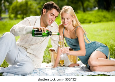 Happy successful attractive couple celebrating together with champagne at picnic, outdoors