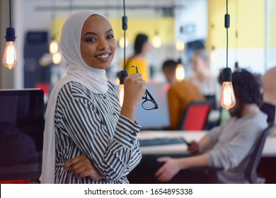 Happy successful business leader posing while her team in background. Young African American business woman standing  and smiling. Teamwork concept